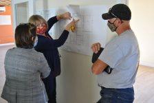 L'architecte, la directrice générale et l'entrepreneur discutent autour des plans de nos futurs bureaux.